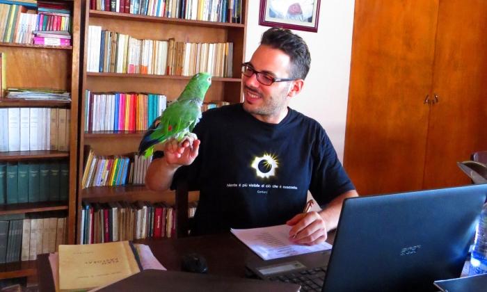 alberto mentre scrive con il pappagallo paco sulla spalla