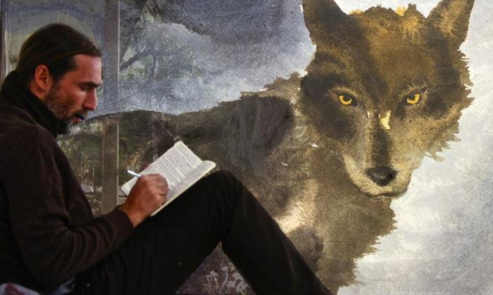 folco mentre scrive con la foto di un lupo sullo sfondo